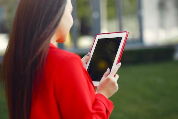 Женщина в красной куртке с помощью планшета