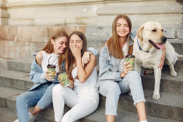 Девушки сидят на лестнице с милой собакой
