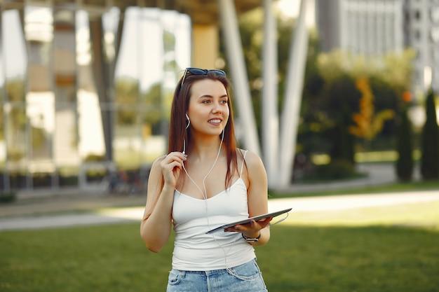 タブレットを使用して大学のキャンパスの女の子