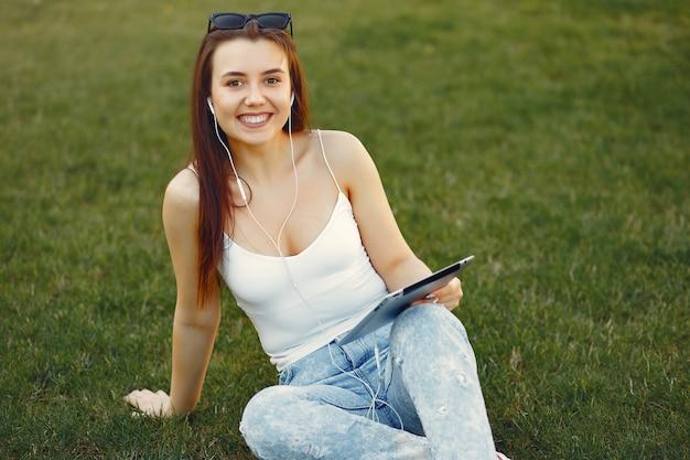 タブレットを使用して大学のキャンパスに座っている女の子