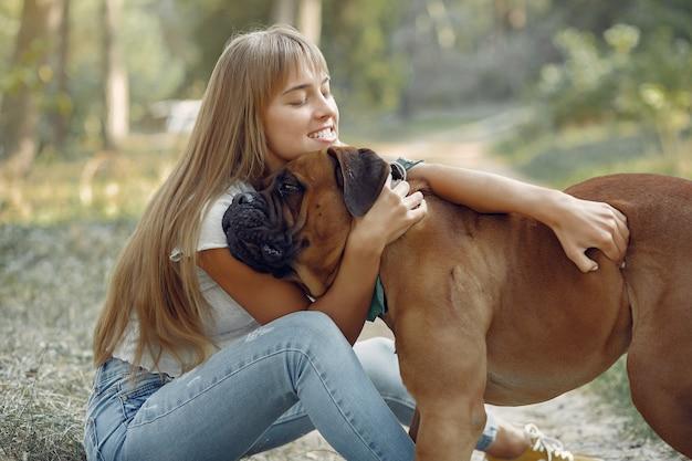 Женщина в летнем лесу играет с собакой