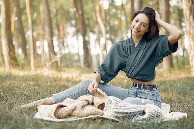 夏の公園に座っていると編み物をする女性