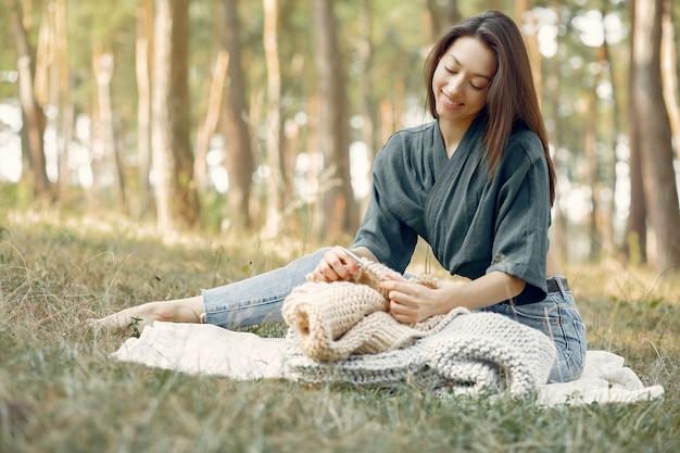 Женщины сидят в летнем парке и вяжут