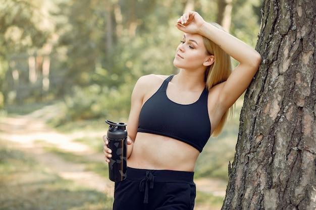 Красивая женщина, стоящая в парке летом с водой