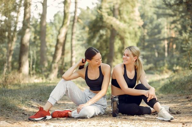 美しい女性は夏の公園で時間を過ごします