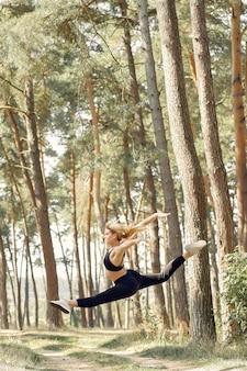 Женщина занимается йогой в летнем лесу