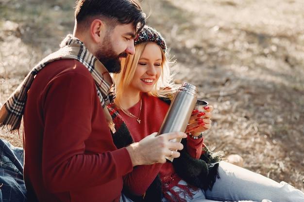 春の森の木のそばに座ってカップル