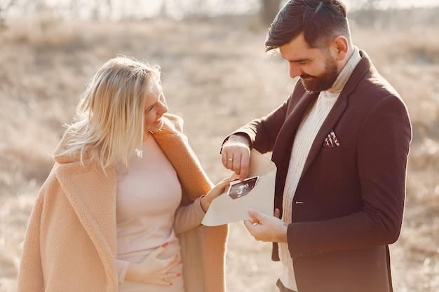 妊娠中の女性が夫と一緒に公園に立っています。