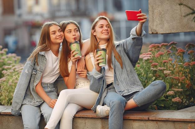 Женщины веселятся на улице и пьют кофе