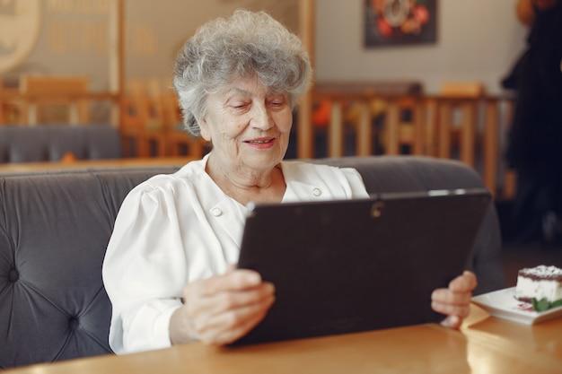 Элегантная пожилая женщина сидит в кафе и использует ноутбук