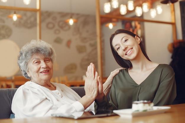 Старая женщина в кафе с молодой внучкой
