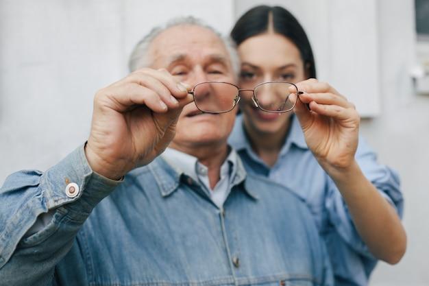 Старик стоит на сером фоне с внучкой