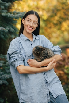 木の背景に立っている青いシャツの女の子
