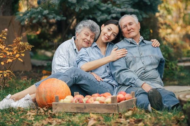 Семья сидит в саду с яблоками и тыквой