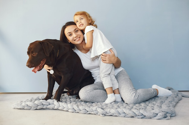 母と娘が自宅で犬と遊ぶ