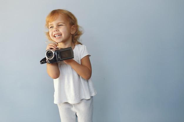 Милая маленькая девочка, сидя в студии на синем фоне