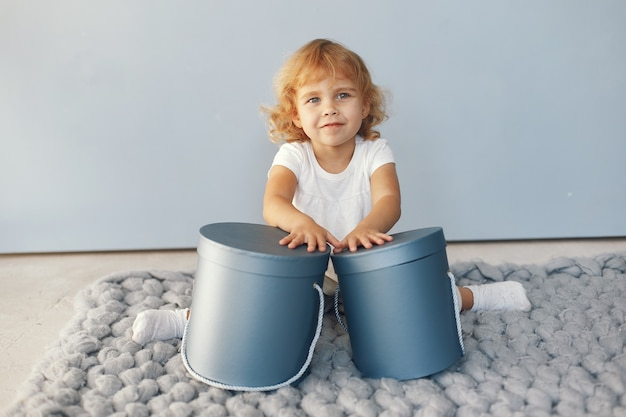 Милая маленькая девочка, сидя в студии с коробкой подарков