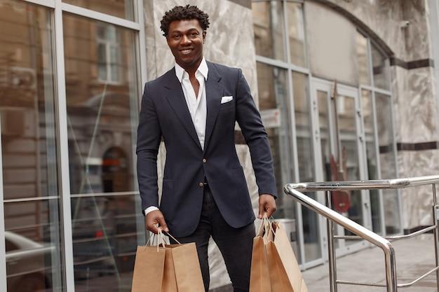 買い物袋が付いている都市のスタイリッシュな黒人男性