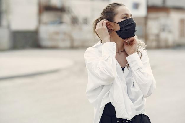 仮面の女が通りに立つ