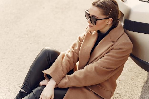 春の街で茶色のコートを着たエレガントな女性