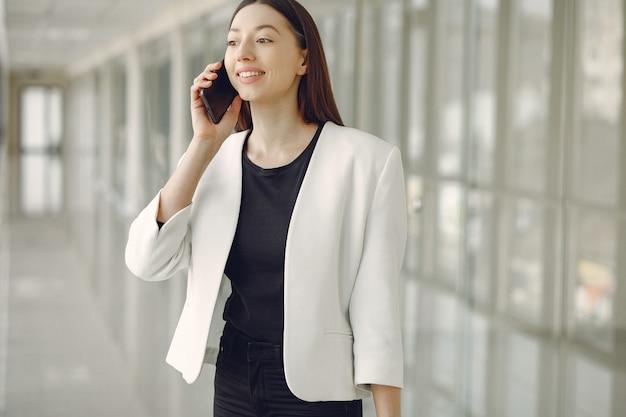 電話でオフィスに立っている女性