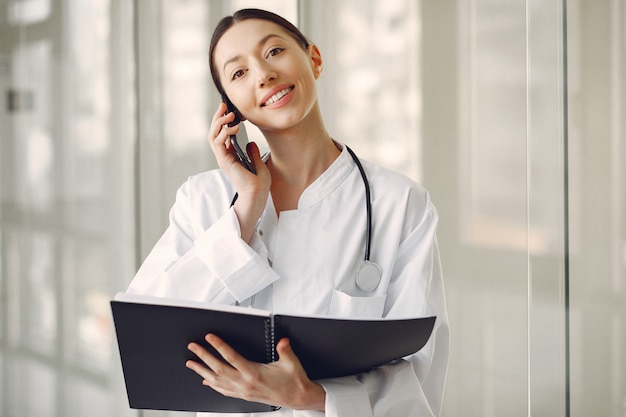 ホールに立っている白い制服を着た女医