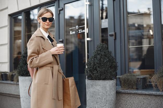 買い物袋と春の街でスタイリッシュな女性