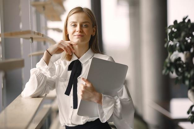 Деловая женщина стоит в офисе с ноутбуком