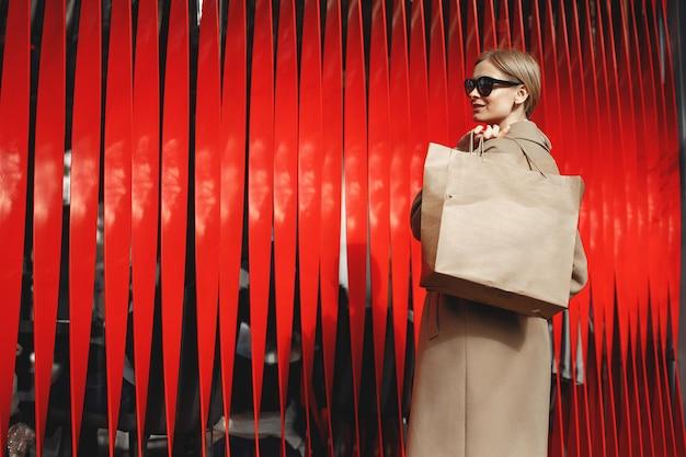 ショッピングバッグで立っている女性