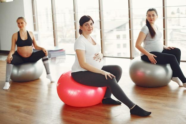 Беременные женщины занимаются йогой в тренажерном зале