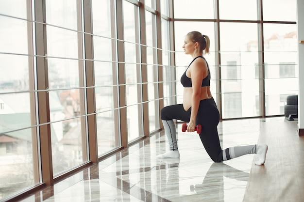 Беременная женщина занимается спортом с гантелями