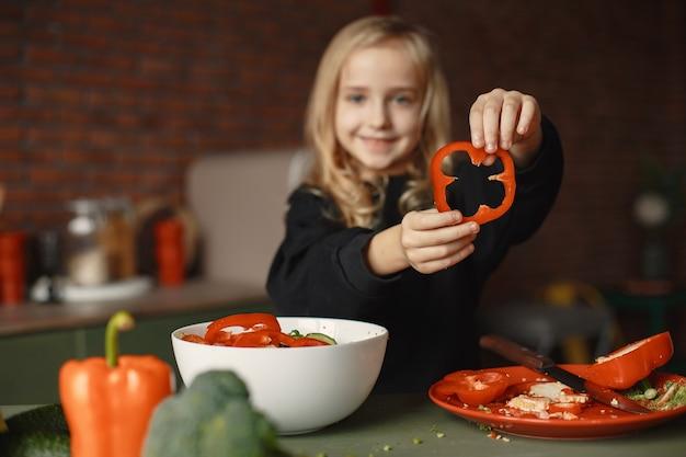 Маленькая девочка готовит салат на кухне