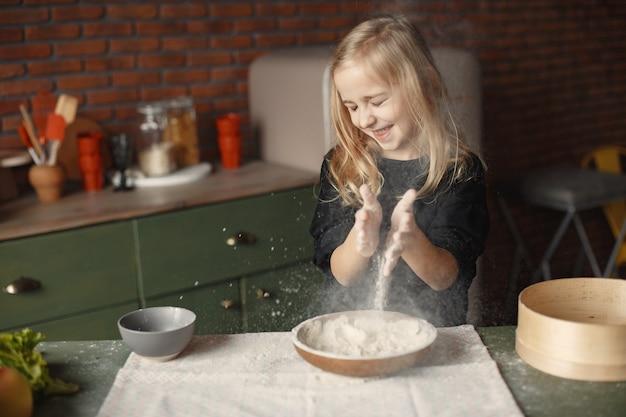 Маленькая девочка готовит тесто для печенья