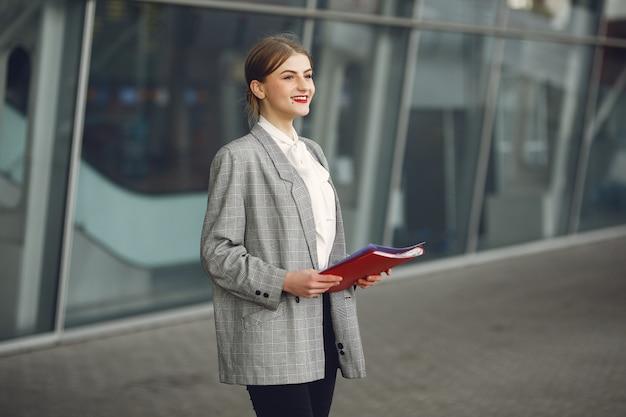 Женщина, стоящая в городе с красной папкой