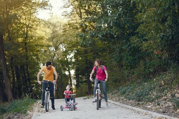 Семья с велосипедом в летнем парке