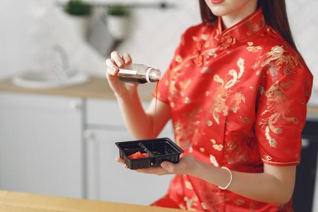 寿司をテーブルに自宅で座っている女の子