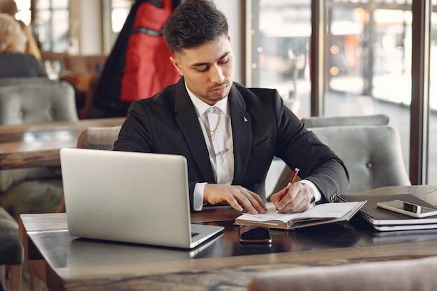 Стильный бизнесмен работает в кафе и использует ноутбук