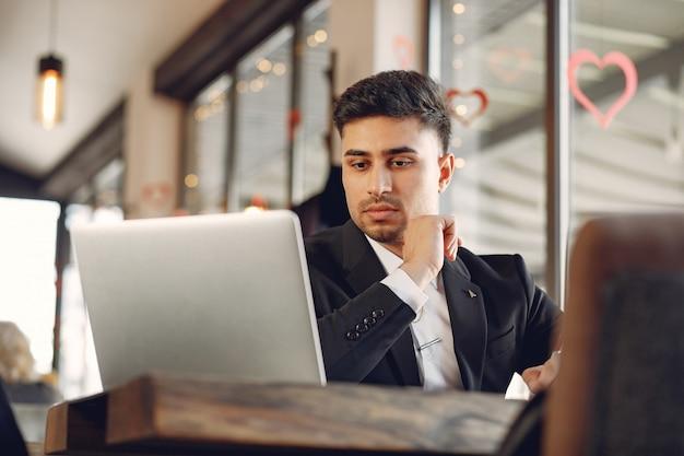カフェで働くスタイリッシュなビジネスマンおよびラップトップを使用