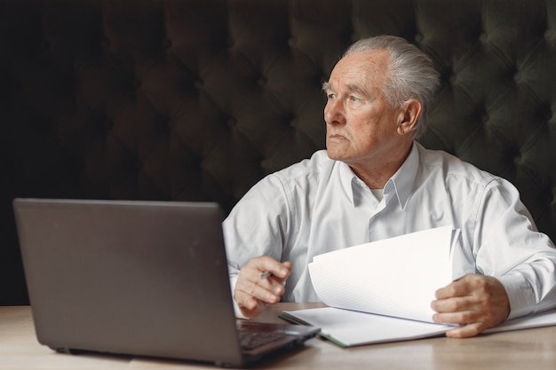 テーブルに座っているとラップトップで働く老人
