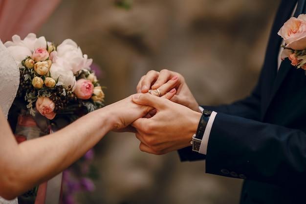 Жених положить кольцо на палец невесты
