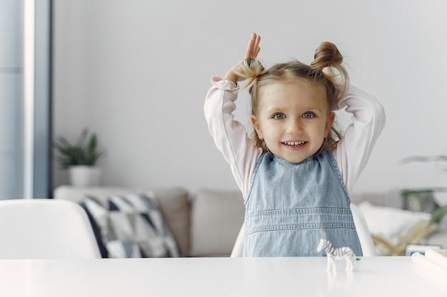 Маленькая девочка сидит на столе с игрушкой