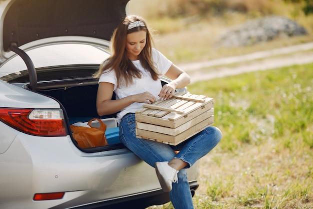 木製の箱でトランクに座っているエレガントな女性