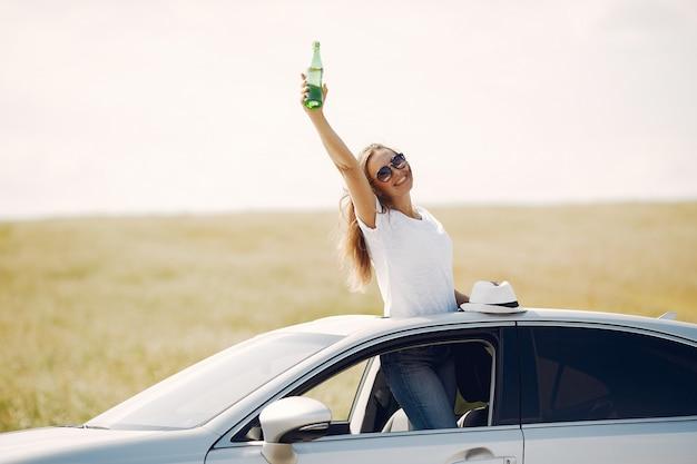 車のハッチに立っているエレガントな女性