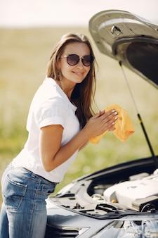 エレガントな女性がぼろで車を拭く