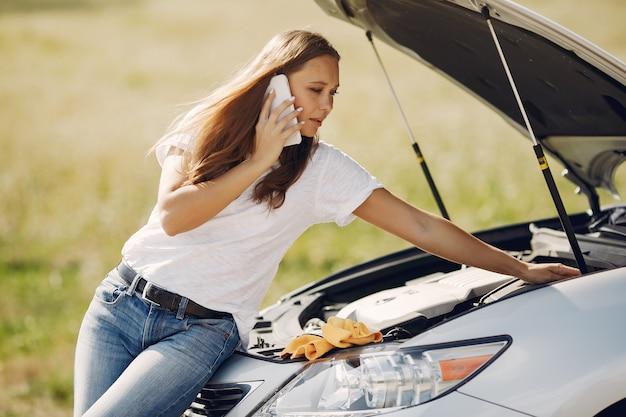壊れた車の近くの女性が助けを求める