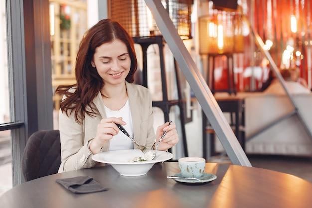 Элегантная женщина сидит за столом с чаем и пастой