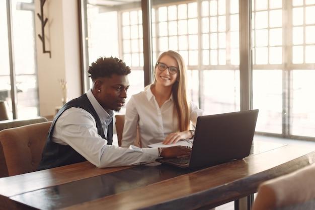 Стильные люди работают в офисе и пользуются ноутбуком