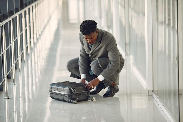 Элегантный темнокожий мужчина в аэропорту с чемоданом