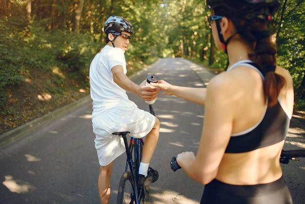 Спортивная пара на велосипедах в летнем лесу