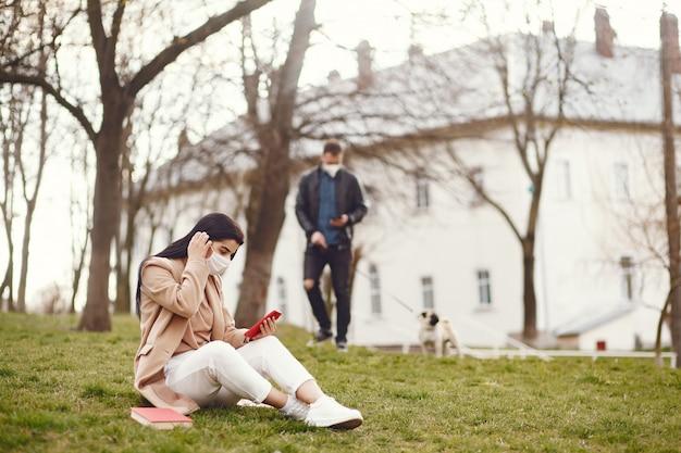 草の上に座っている仮面の女